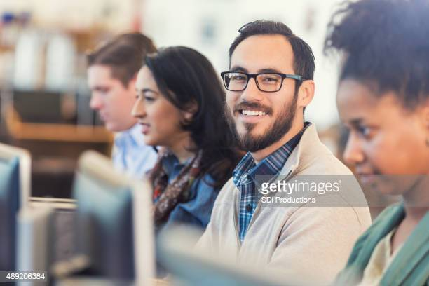 Happy Hispanic hipster man using comptuer in college computer class