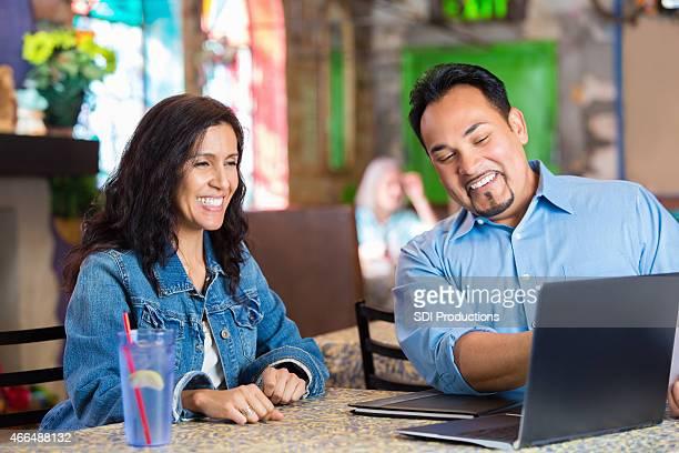 Glückliche Hispanic restaurant Eigentümer, die fincancial Bericht während der Tagung