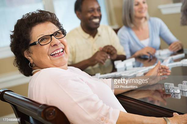 Happy Hispanic senior woman playing dominoes with friends