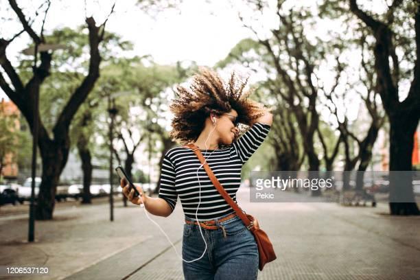 glückliche hispanische frau hört musik und tanzt auf der straße - frauenpower stock-fotos und bilder