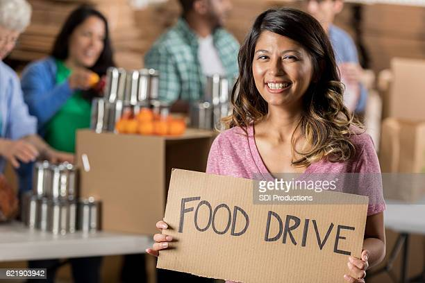Happy Hispanic woman with 'Food Drive' sign