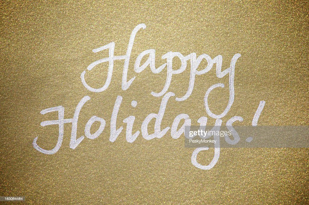 Happy holidays message greeting card silver on sparkly gold paper stock photo