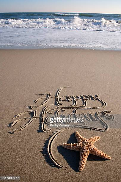 Happy Holidays Message Handwritten on Beach with Crashing Waves