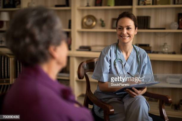 Happy home caregiver talking to old woman at home.