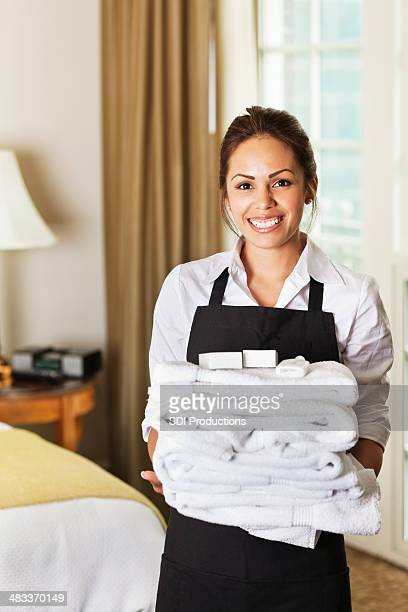 Happy hotel maid with towels in a guest room