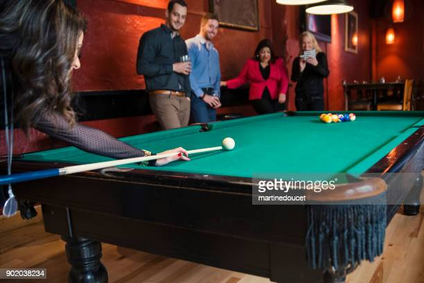 Happy hour for friends and coworkers in a bar playing pool.