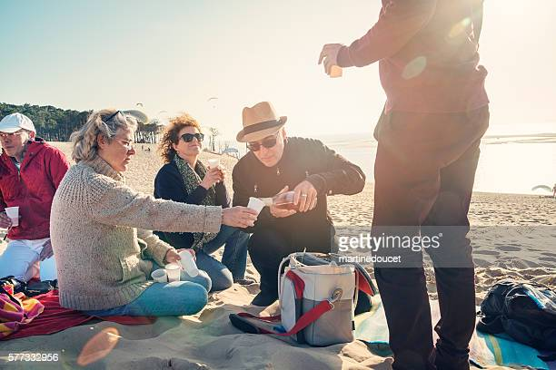 Happy hour for group of friends on beach in spring.