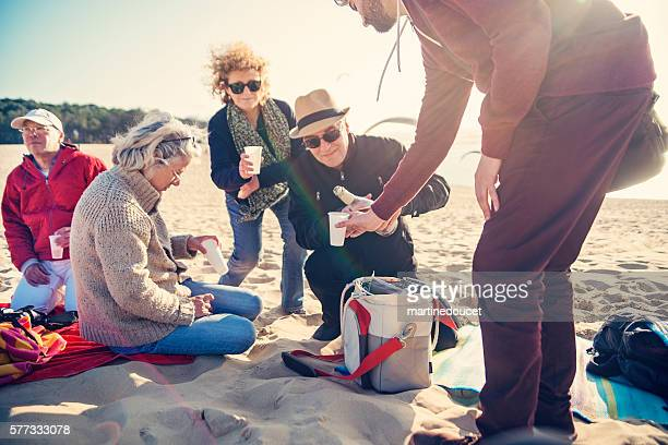 """happy hour for group of friends on beach in spring. - """"martine doucet"""" or martinedoucet stock pictures, royalty-free photos & images"""