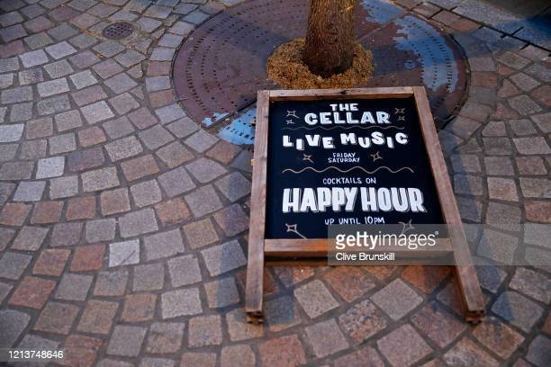 Happy Hour sign lies on the ground outside the Cellar bar in Altrincham Cheshire which will now have to close tonight on March 20, 2020 in...