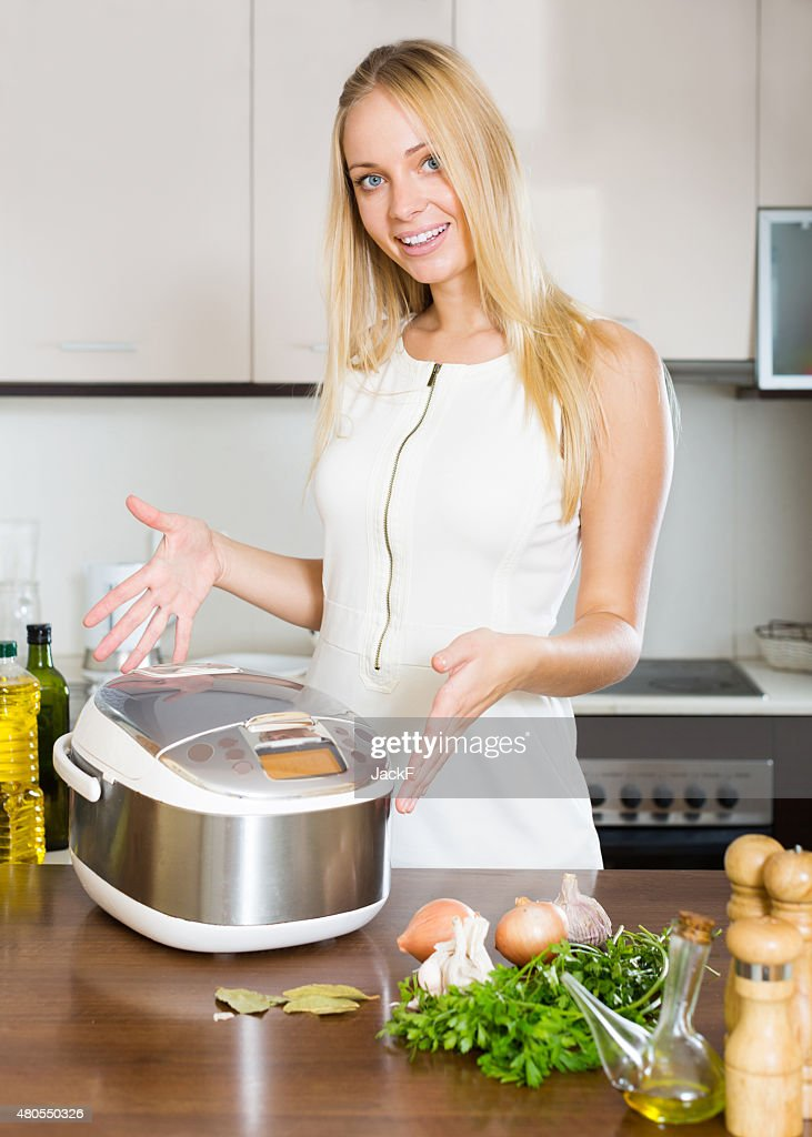 Happy housewife cooking : Stock Photo