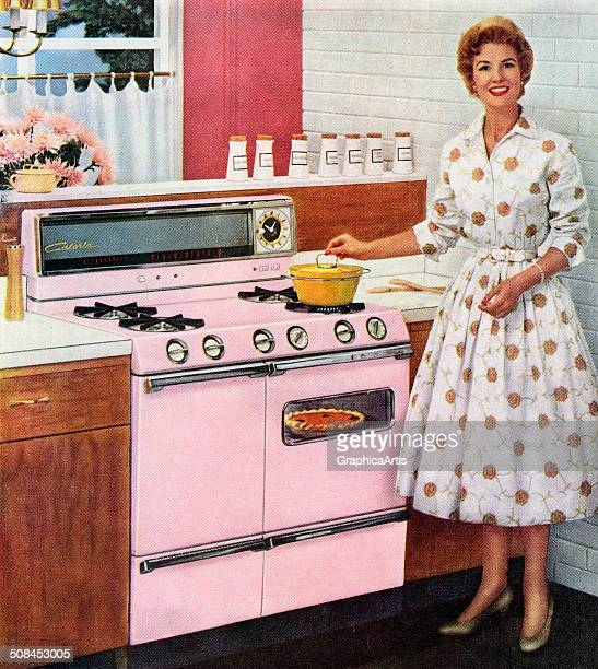 Happy housewife cooks on her new pink range, with a pot on the cooktop and a pumpkin pie in the oven, 1957. Screen print.
