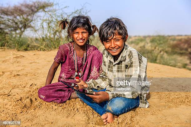 Happy Indian children using digital tablet, desert village, India