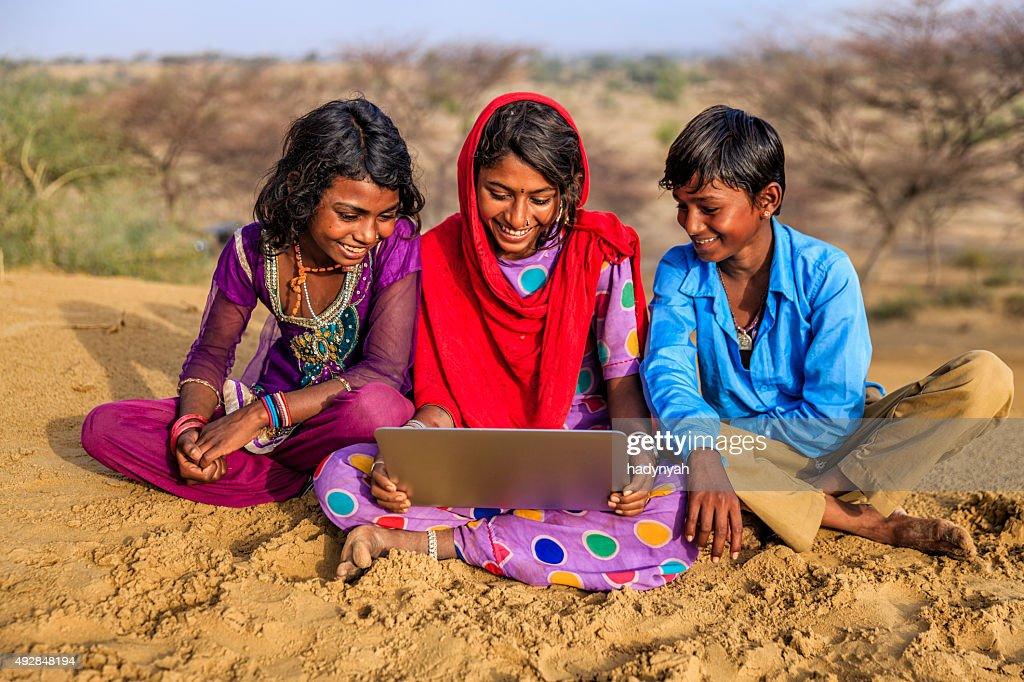 Happy Indian children using laptop, desert village, India : Stock Photo