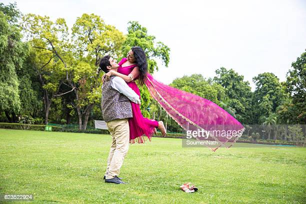 Happy Indian couple - Man lifting and hugging the woman