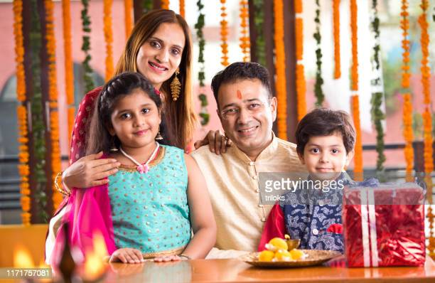 happy indian family in traditional clothing - diwali sweets stock photos and pictures