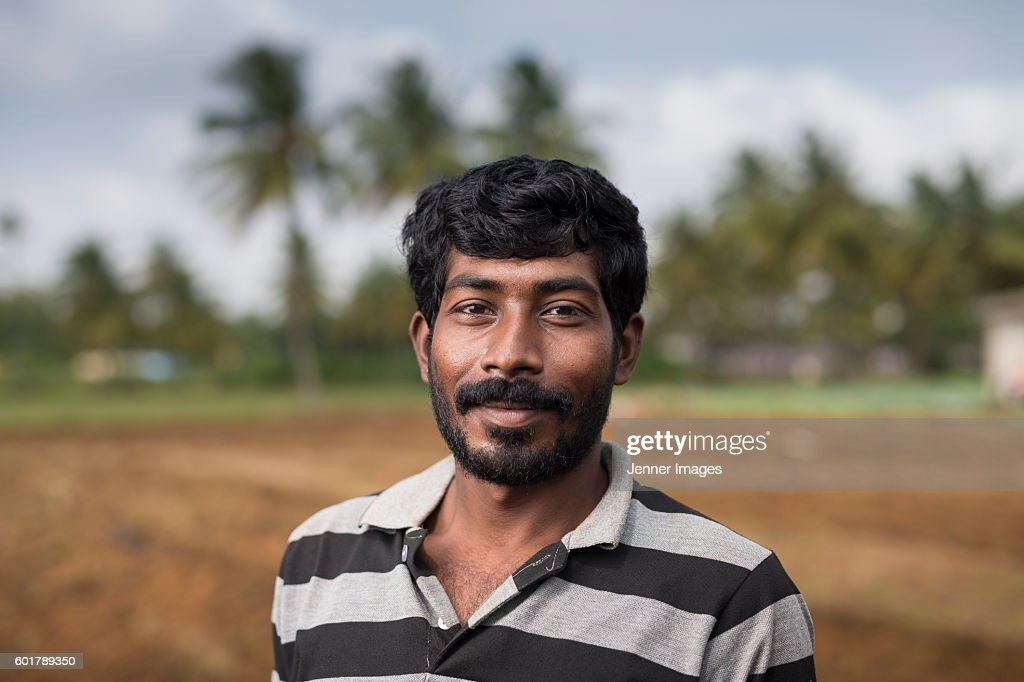 Happy Indian farmer standing in a field. : Stock Photo