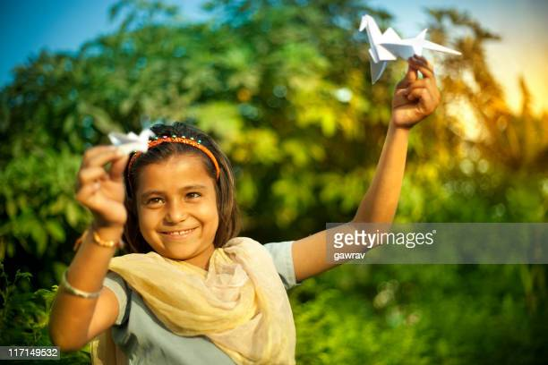 Happy Indian girl playing with paper birds in nature