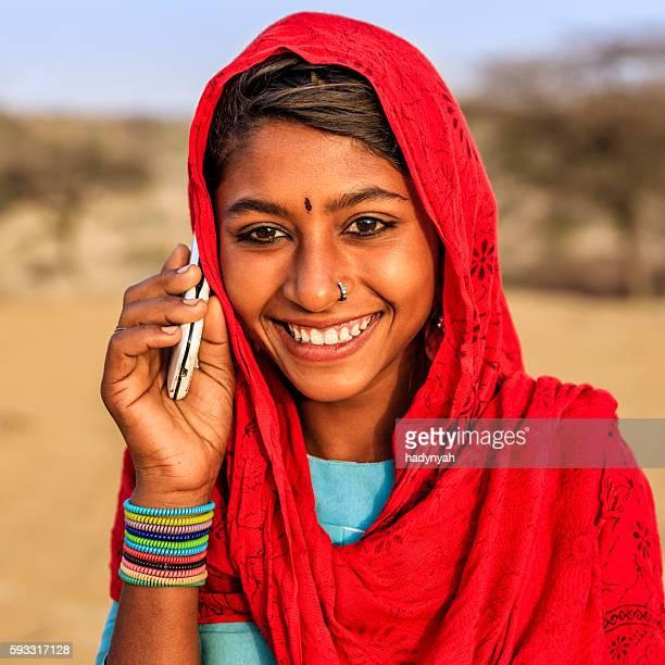 Happy Indian girl using mobile phone in desert village, India