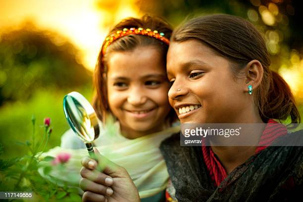 Happy Indian girls exploring something in nature with magnifying glass