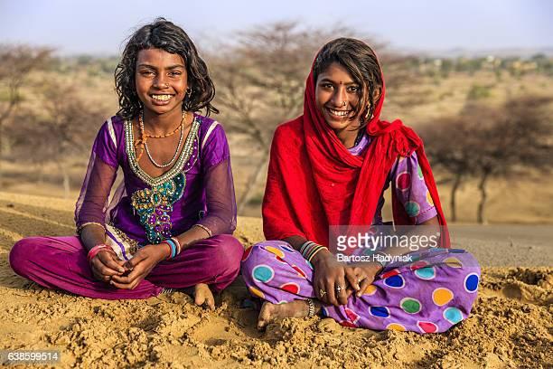 Happy Indian girls sitting on sand dune, desert village, India