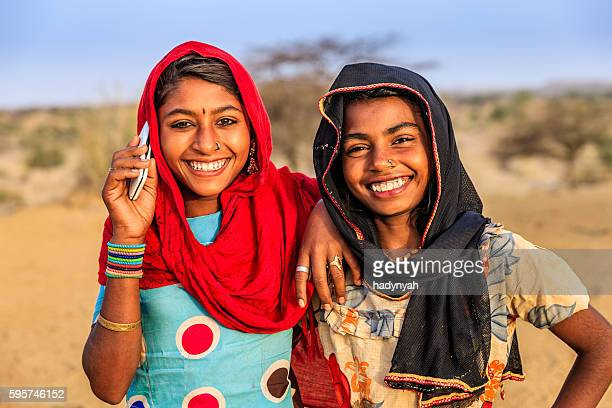 Happy Indian girls using mobile phone in desert village, India