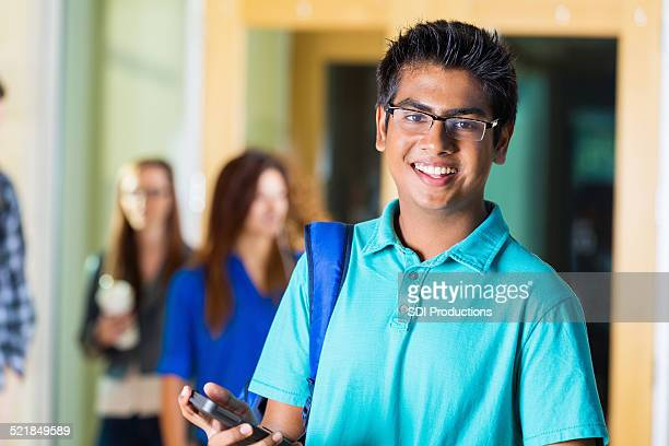 Happy Indian high school student using phone outside classroom