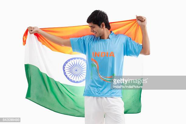 Happy Indian hockey player with Indian flag isolated over white background