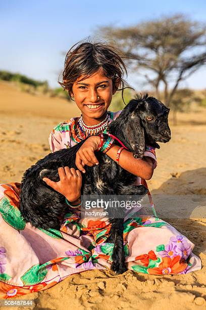 Happy Indian little girl holding a goat, desert village, India