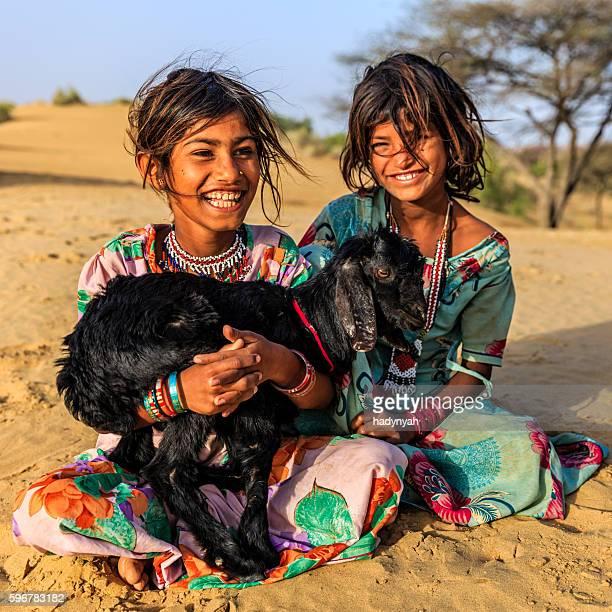 Happy Indian little girls holding a goat, desert village, India