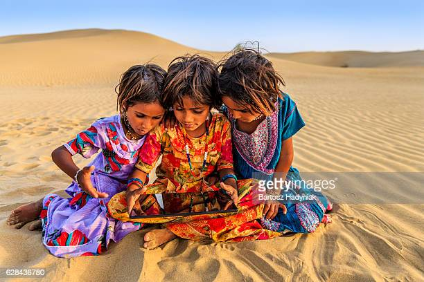 Happy Indian little girls using digital tablet, desert village, India