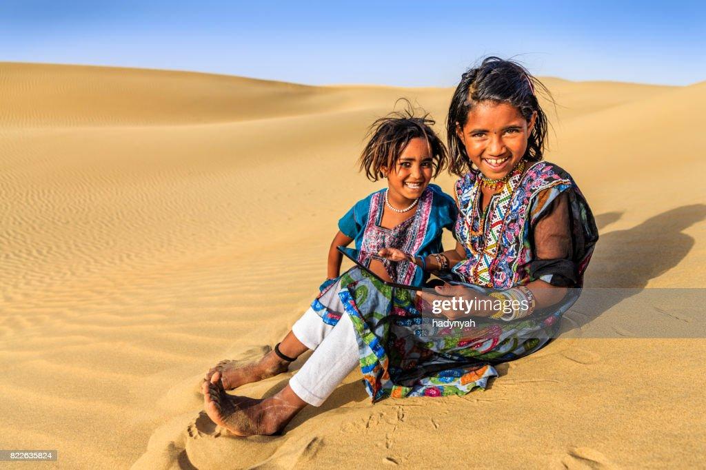 Happy Indian little girls using digital tablet, desert village, India : Stock Photo