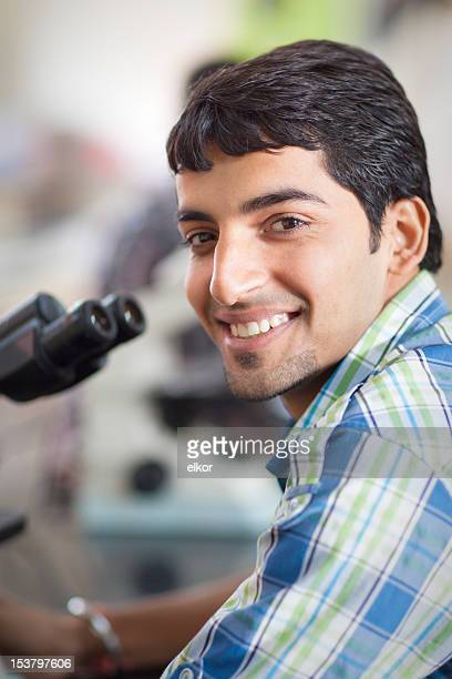 Happy Indian Student With Microscope In A Laboratory
