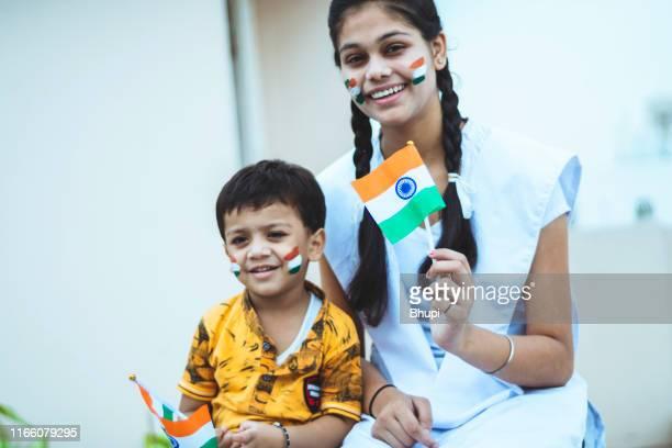 誇りを持って国旗を持つ小さな男の子と幸せなインドのティーンエイジャーの女の子 - フェイスペイント ストックフォトと画像