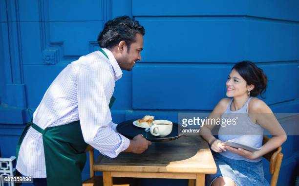 Happy Indian waiter serving woman at a cafe