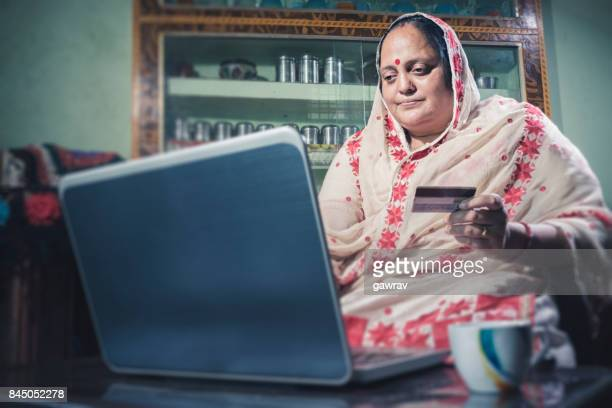 Happy Indian woman doing online shopping at home.