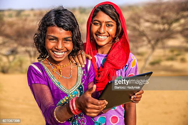 Happy Indian young girls using digital tablet, desert village, India