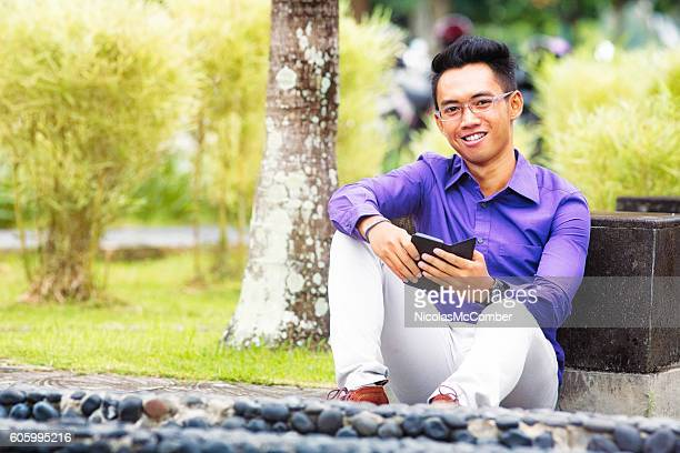 Happy Indonesian male student outdoors portrait with mobile phone