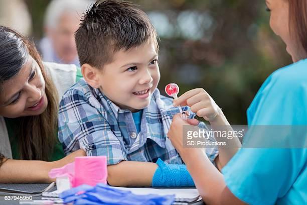 Happy injured boy gets lollipop after medical exam