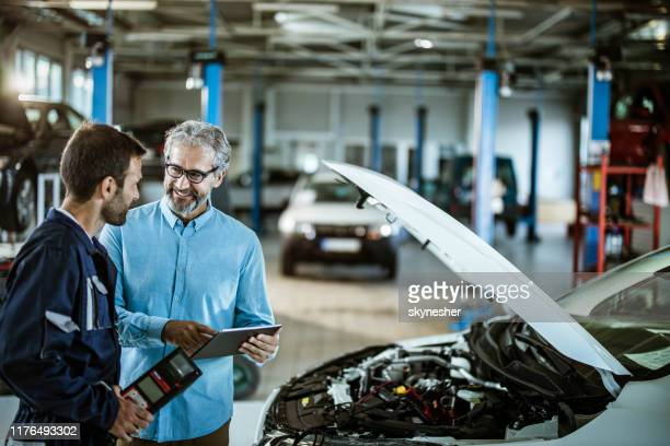 happy inspector using touchpad and talking to a mechanic in auto repair shop. - touchpad stock pictures, royalty-free photos & images