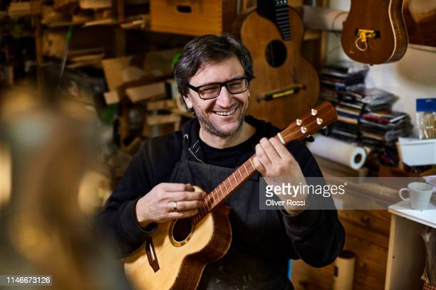 happy instrument maker playing on ukulele in his workshop - guitar stock pictures, royalty-free photos & images