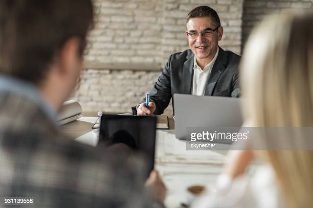 happy insurance agent having a meeting with his customers in the office. - financial advisor stock photos and pictures