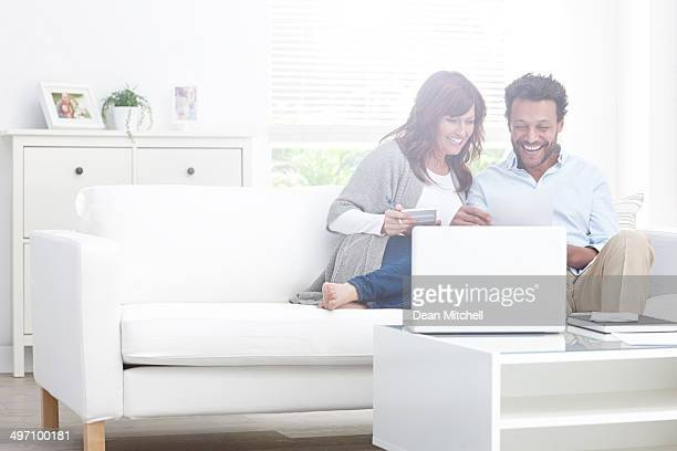 Happy interracial couple calculating domestic bills at home