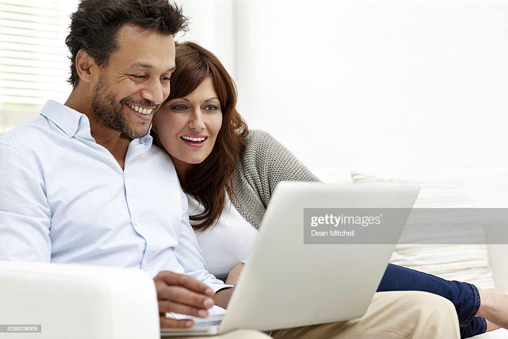 Happy interracial couple using laptop : Stock Photo