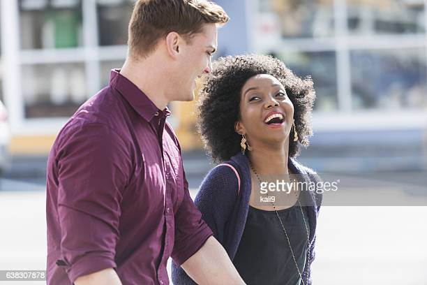 Happy interracial couple walking, holding hands laughing