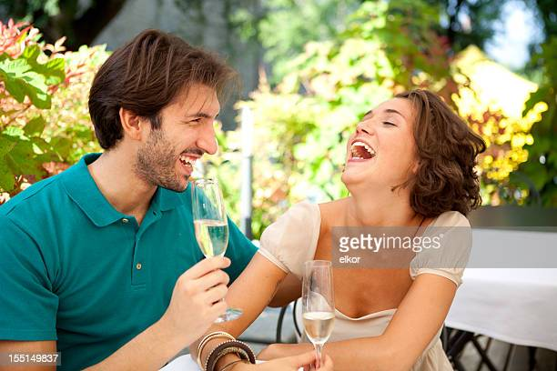 Happy Italian couple laughing in an outdoor restaurant