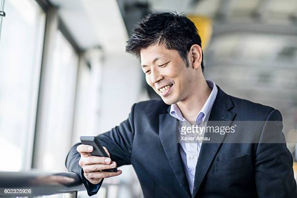 Happy Japanese businessman looking at his phone at the station