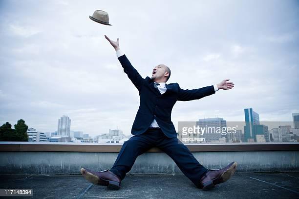 Happy japanischen Geschäftsmann Herumwerfen seinen Hut in der Luft