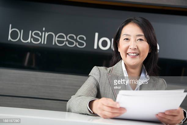 Happy Japanese businesswoman working in business lounge
