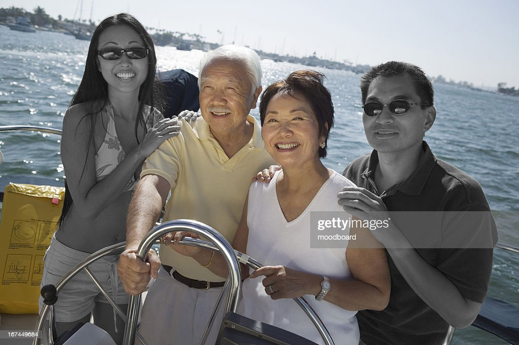 Happy Japanese family sailing together on yacht : Stock Photo