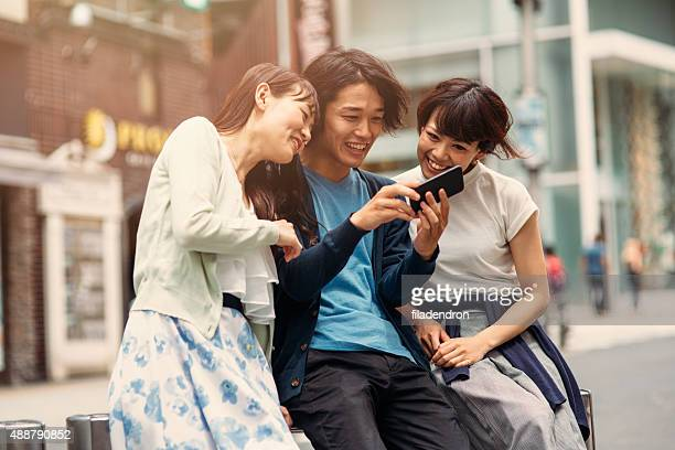 Happy japanese friends surfing the net